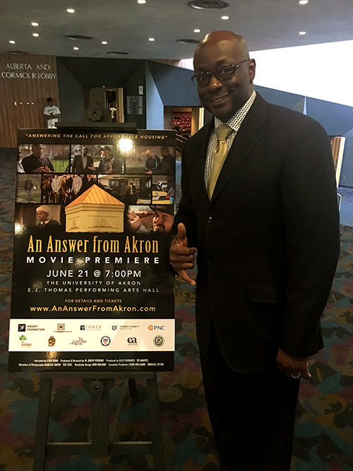 Jermel Wilkerson Sr. standing next to poster